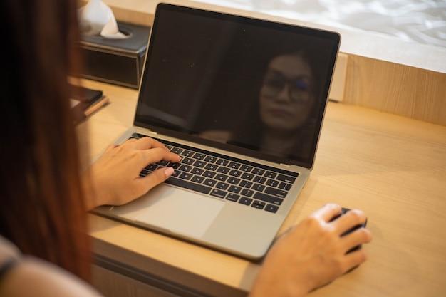 Vista traseira da mulher conversa com o parceiro usando videochamada no laptop.
