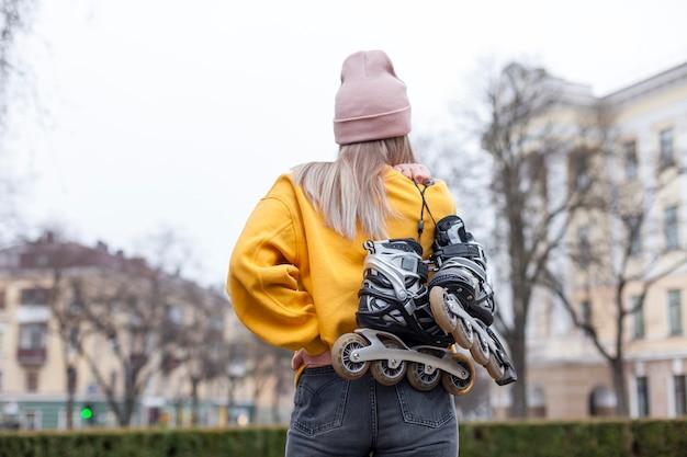 Vista traseira da mulher de gorro carregando patins