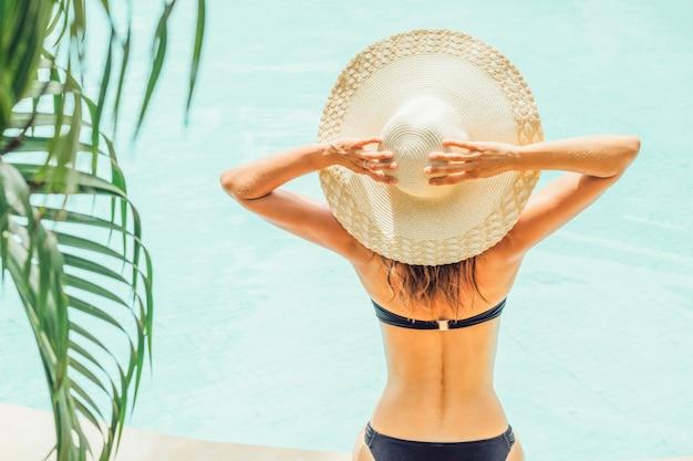 Vista traseira da mulher de maiô e chapéu perto da piscina