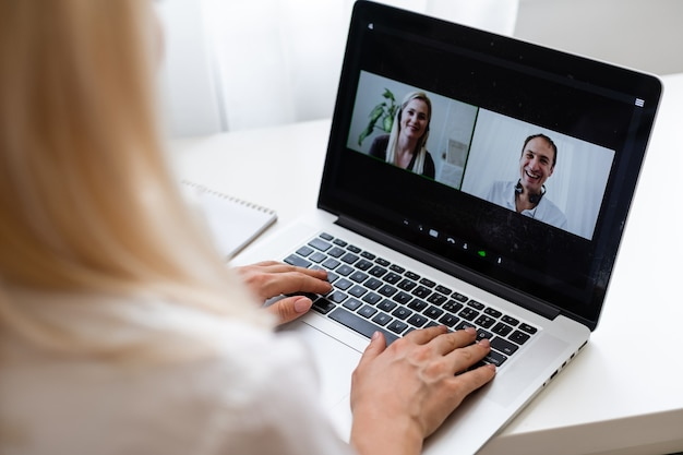 Vista traseira da mulher de negócios, falando com seus colegas sobre o plano de vídeo-conferência. equipe de negócios multiétnica usando laptop para uma reunião online em videochamada. grupo de pessoas inteligentes trabalhando em casa
