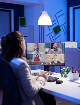Vista traseira da mulher de negócios, falando sobre o relatório de venda em videoconferência, trabalhando horas extras no escritório de start-up. equipe usando comunicação sem fio online discutindo na webcam durante a reunião de grupo.