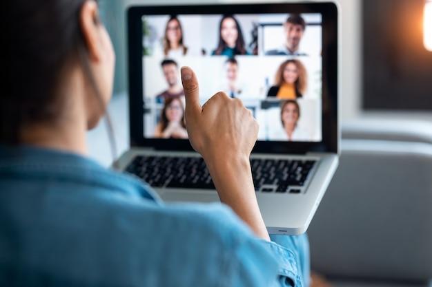 Vista traseira da mulher de negócios fazendo videochamada e mostrando o polegar para o laptop no briefing online enquanto está sentado no sofá em casa.