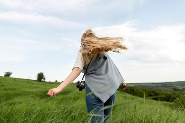 Vista traseira da mulher desfrutando de ar fresco na natureza