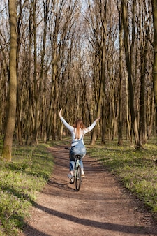 Vista traseira da mulher despreocupada, andar de bicicleta na floresta