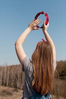 Vista traseira da mulher despreocupada tocando pandeiro na natureza
