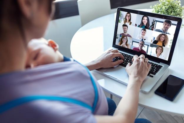 Vista traseira da mulher e do filho bebê fazendo reunião on-line com colegas de trabalho em videochamada no laptop em casa.