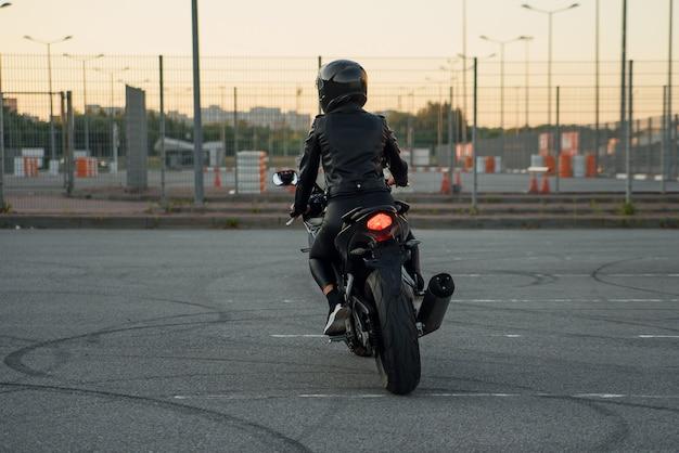 Vista traseira da mulher elegante em jaqueta de couro preta, calças e capacete protetor monta em motocicleta esportiva no estacionamento urbano ao ar livre.