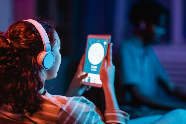 Vista traseira da mulher em casa usando fones de ouvido e tablet
