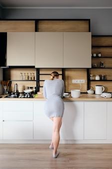 Vista traseira da mulher em pé ao lado de uma cozinha moderna