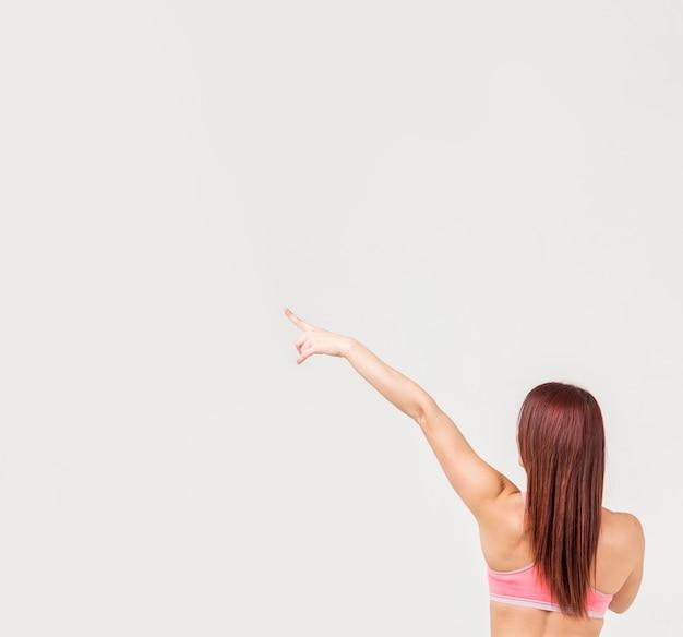 Vista traseira da mulher em roupas de ginástica, apontando para o canto esquerdo
