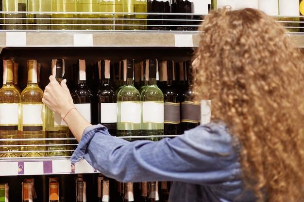 Vista traseira da mulher encaracolada escolhe vinho na prateleira no supermercado, prepara-se para férias ou dia especial, faz a compra. ondulado bonito jovem fêmea seleciona bebida alcoólica em shopping