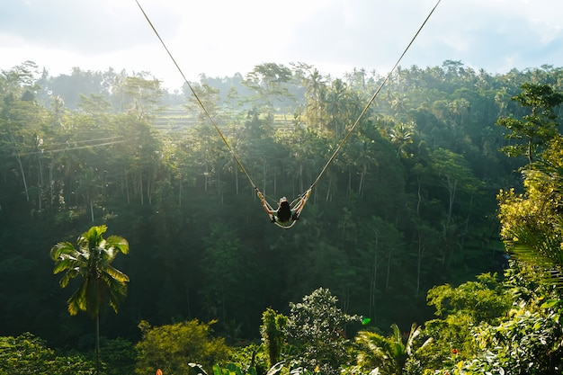 Vista traseira da mulher enquanto balanço com fundo de floresta natural na luz solar