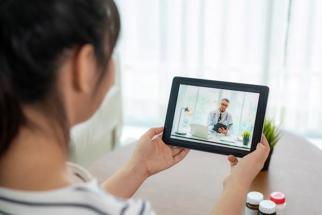Vista traseira da mulher fazendo videochamada com o médico dela enquanto fica em casa.
