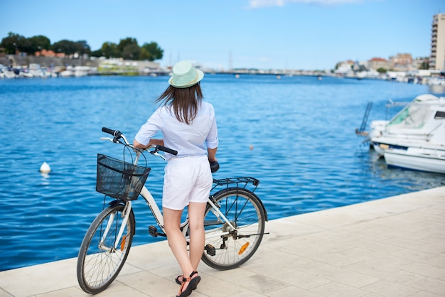 Vista traseira da mulher fica encostado na bicicleta na calçada pedregosa
