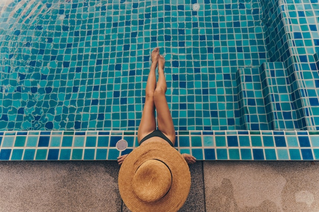 Vista traseira da mulher graciosa em traje de banho e chapéu, sentado perto da piscina