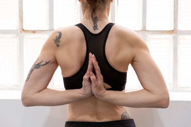 Vista traseira da mulher irreconhecível em pé com as mãos namaste nas costas e fazendo ioga em casa.