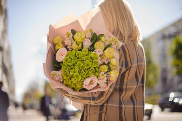 Vista traseira da mulher loira com casaco xadrez com um grande buquê verde de flores