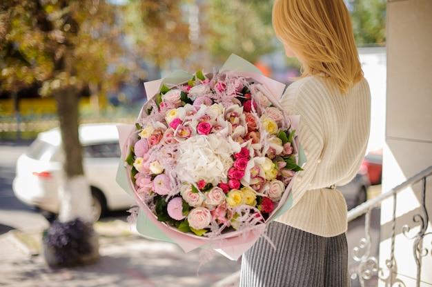 Vista traseira da mulher loira de suéter branco com um grande buquê brilhante de flores