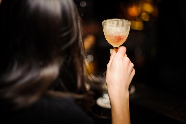 Vista traseira da mulher morena segurando um copo com cocktail