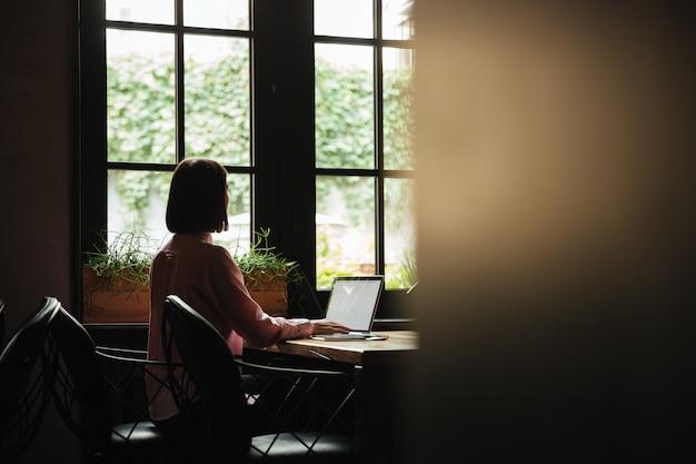 Vista traseira da mulher morena sentada à mesa perto da janela