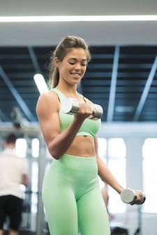 Vista traseira da mulher morena treinando no ginásio.