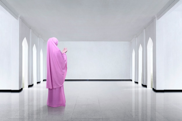 Vista traseira da mulher muçulmana asiática, levantando a mão e rezando