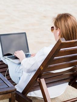 Vista traseira da mulher na cadeira de praia, trabalhando no laptop