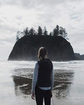 Vista traseira da mulher na praia com penhasco