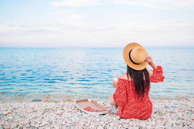 Vista traseira da mulher na praia no piquenique, olhando para o mar