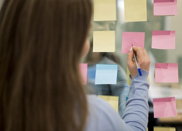 Vista traseira da mulher no escritório escrevendo sobre notas autoadesivas