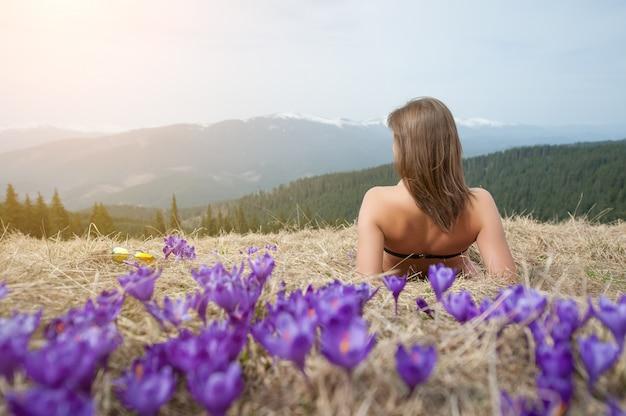 Vista traseira da mulher nua em traje de banho está deitado na grama de primavera quase açafrões na montanha