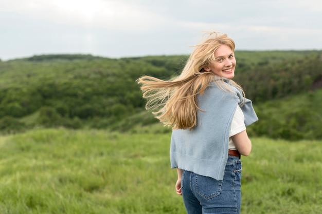 Vista traseira da mulher posando ao ar livre na natureza