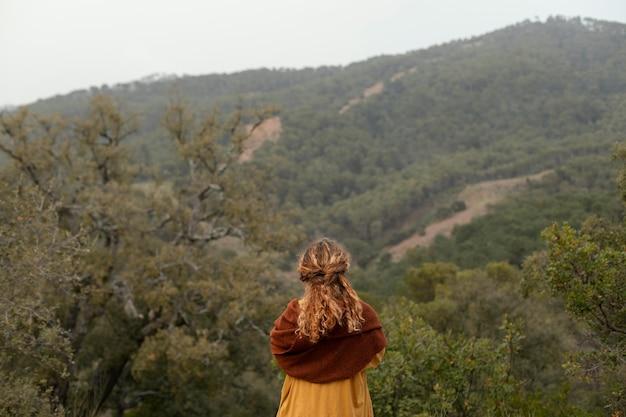 Vista traseira da mulher posando ao ar livre