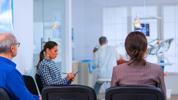 Vista traseira da mulher preenchendo o formulário dentário sentado no chiar na sala de espera, preparando-se para os implantes dentários, enquanto o paciente de isenção do médico no fundo. consultório ortodontista profissional lotado.