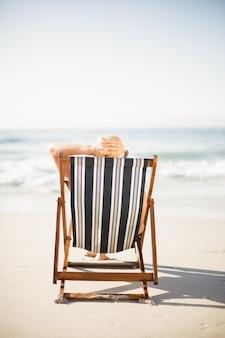 Vista traseira da mulher relaxante na praia