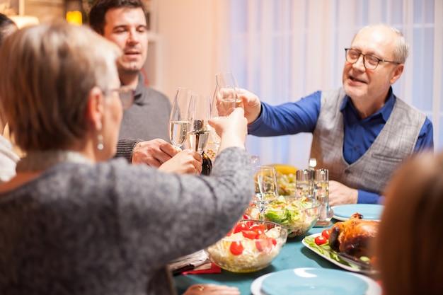 Vista traseira da mulher sênior tilintando uma taça de vinho com a família no jantar de natal.