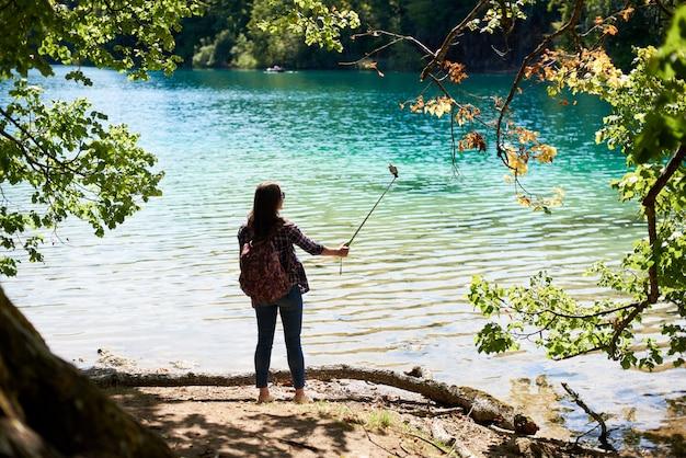 Vista traseira da mulher turista com mochila em pé na margem do lago tirando foto