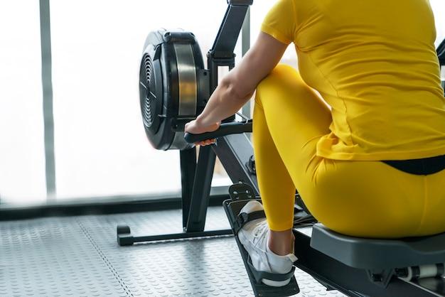 Vista traseira da mulher usa uma máquina de remo