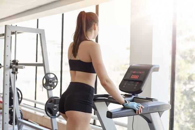 Vista traseira da mulher vestindo sutiã esportivo preto e curto, estar em ação, exercitar-se no health club, cabe jovem correndo na esteira na academia, garota tentando mantém a forma, cuidando de sua saúde.