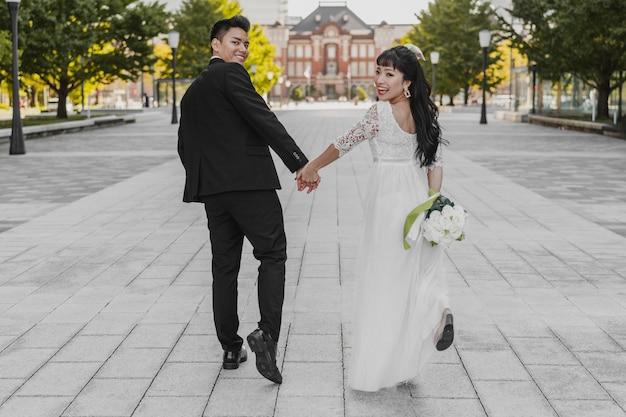 Vista traseira da noiva e do noivo caminhando pela rua de mãos dadas