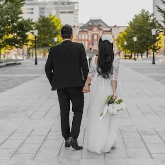 Vista traseira da noiva e do noivo caminhando pela rua