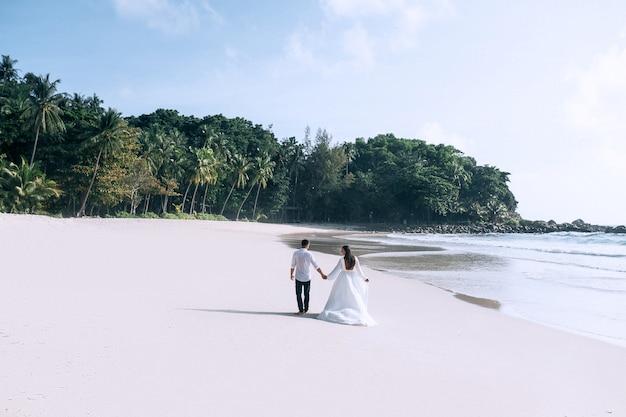Vista traseira da noiva e do noivo de mãos dadas e caminhando na praia