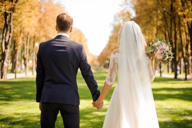 Vista traseira da noiva e do noivo de mãos dadas