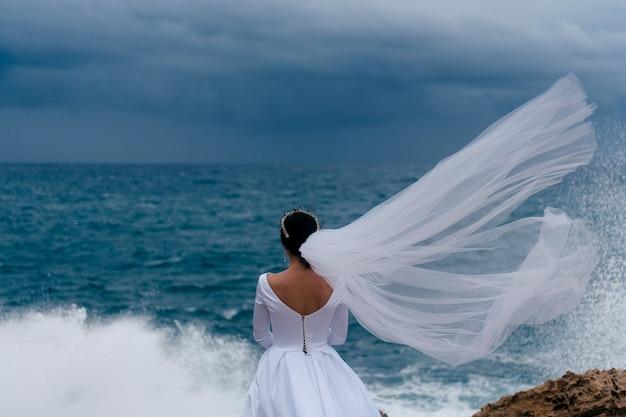 Vista traseira da noiva morena com vestido de noiva branco e véu de noiva em um dia nublado