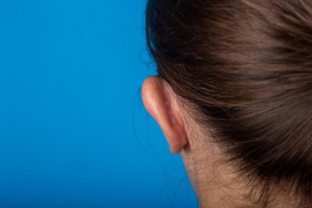 Vista traseira da orelha com orelhas de orelha da jovem em um fundo azul. otoplastia, cirurgia.