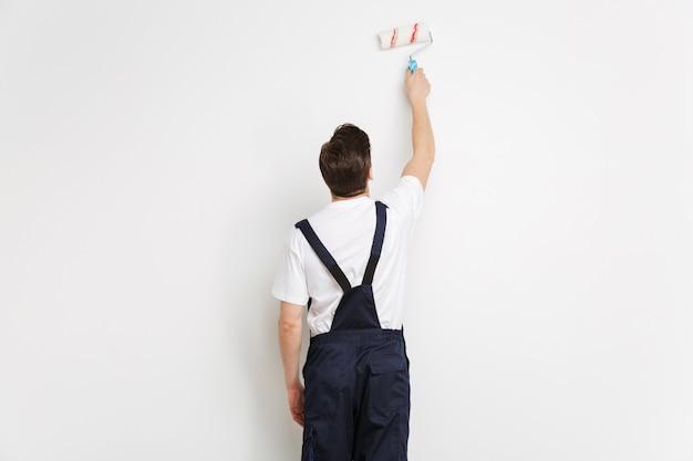 Vista traseira da parede do jovem construtor masculino com rolo de tinta sobre a parede cinza