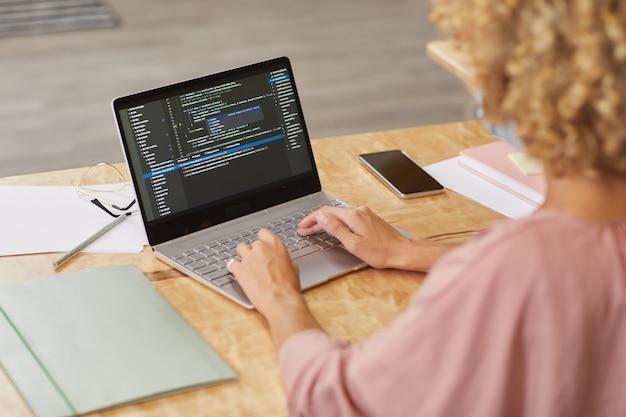 Vista traseira da programadora sentada à mesa digitando no laptop, ela testando um novo programa de computador
