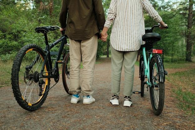 Vista traseira da seção baixa de um jovem casal de ciclistas em trajes casuais em pé na estrada cônica com agulhas de coníferas entre árvores verdes