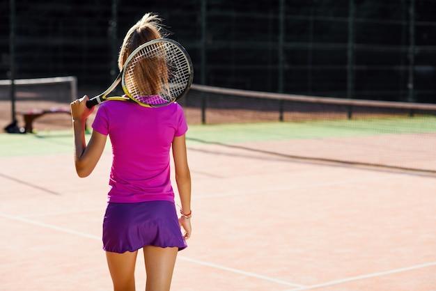 Vista traseira da tenista atraente de uniforme com raquete de tênis andando na quadra de tênis ao ar livre no fundo por do sol.