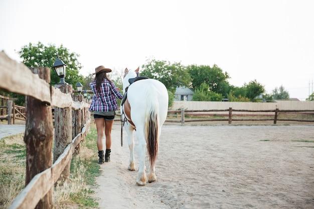 Vista traseira da vaqueira mulher caminhando com o cavalo na aldeia